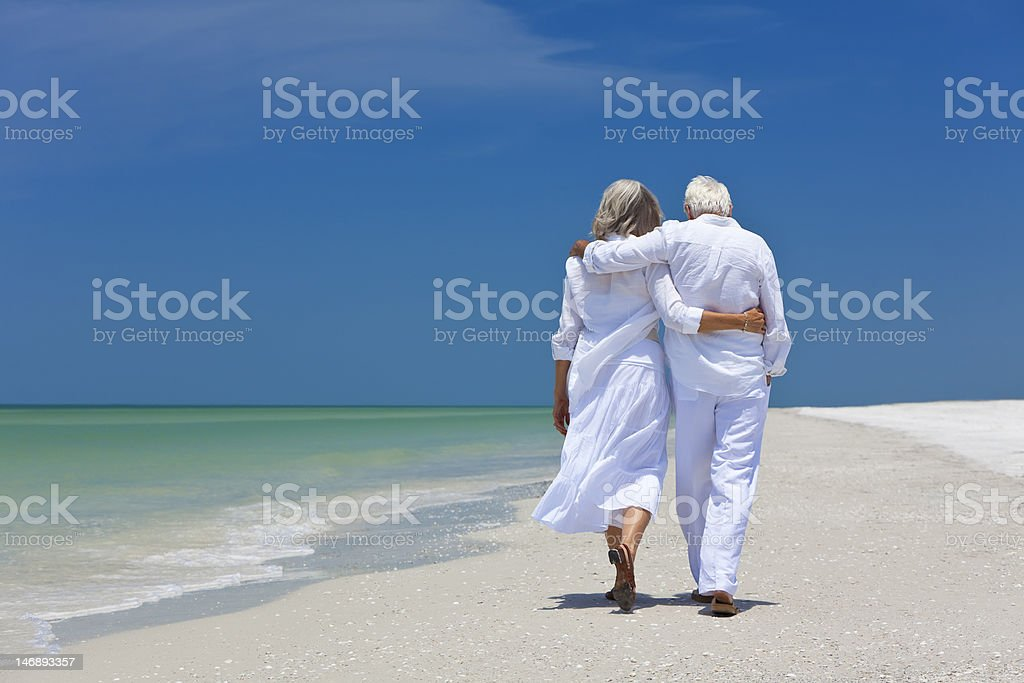 Rear view of senior couple walking on beach stock photo