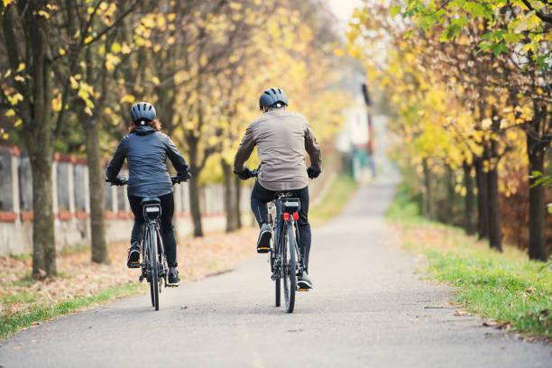 eine rückansicht von älteres paar mit elektrobikes radfahren im freien auf einer straße. - elektrorad stock-fotos und bilder