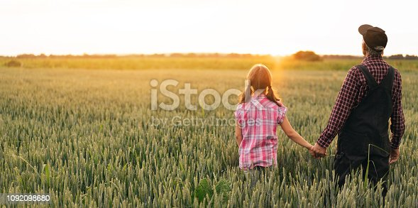 Rear view of senior farmer showing to his granddaughter a wheat field, holding hands.