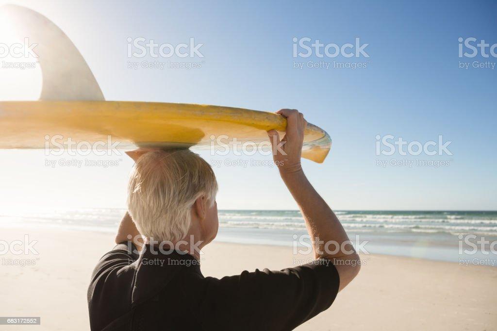 老人頭在海灘上進行衝浪板的後視圖 免版稅 stock photo