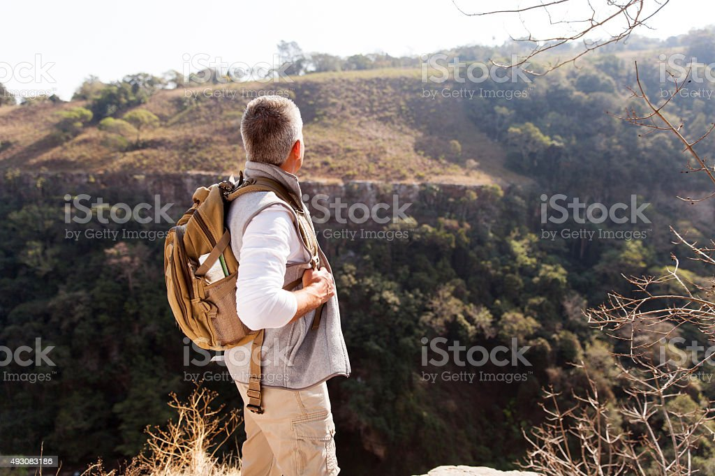 rear view of senior man with backpack stock photo