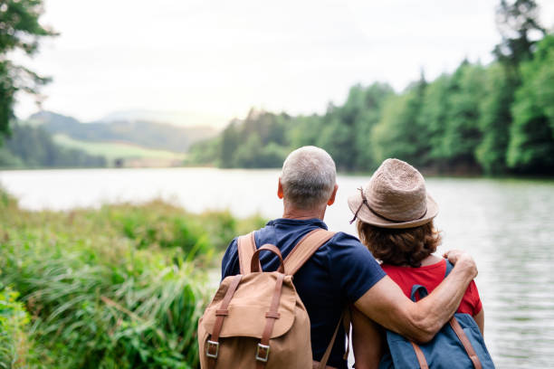 Rear view of senior tourist couple on a walk in nature, standing by lake. stock photo