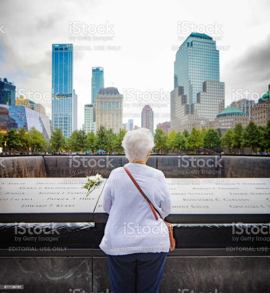 Rear view of Senior woman grieving at World trade center 9/11 memorial site stock photo