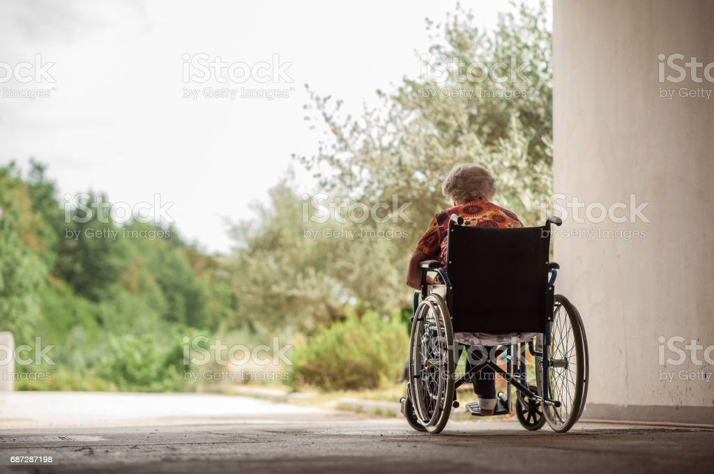 Rear View Of Senior Woman On Wheelchair In The Garage Corridor stock photo
