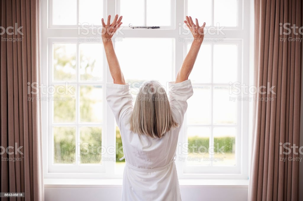 Rear View Of Senior Woman Stretching In Front Of Bedroom Window stock photo