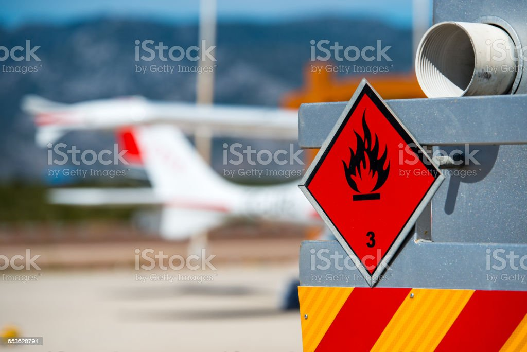 Rear view of service and refuelling truck on an airport with an aircraft in the blurry background. Chemical hazard, flammable liquids. stock photo
