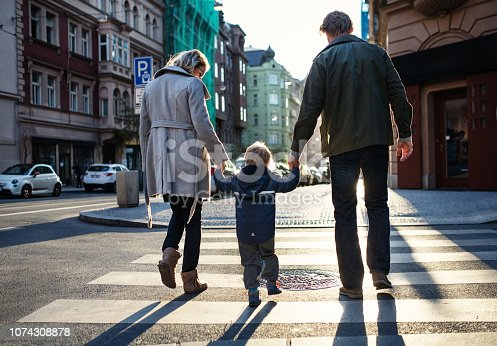 A rear view of small toddler boy with parents crossing a road outdoors in city, holding hands.