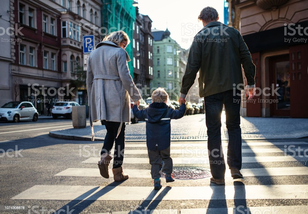 A rear view of small toddler boy with parents crossing a road outdoors in city. stock photo
