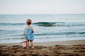 A rear view of small toddler girl standing on sand beach on summer holiday. Copy space.