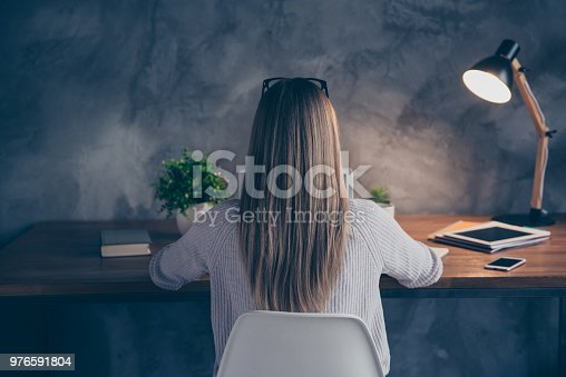 1151920695 istock photo Rear view of smart corporate woman with long hair spectacles on head working late in dark room, expertising analyzing online, chatting with friends in social networks sitting in work place station 976591804