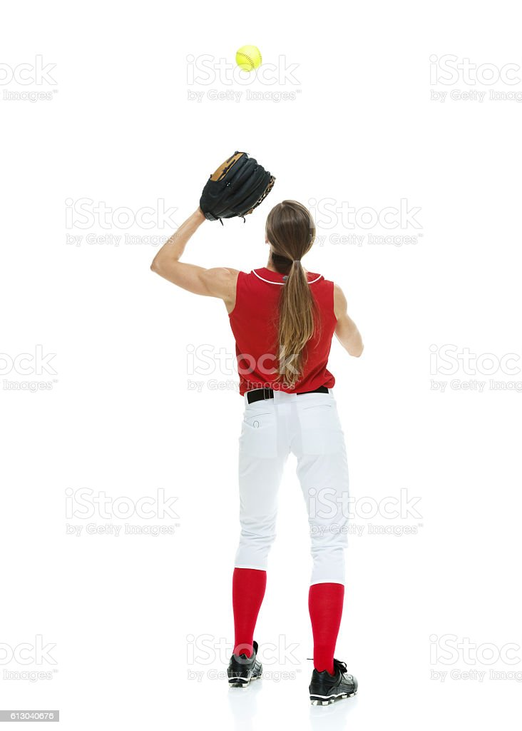 Rear view of softball player throwing stock photo