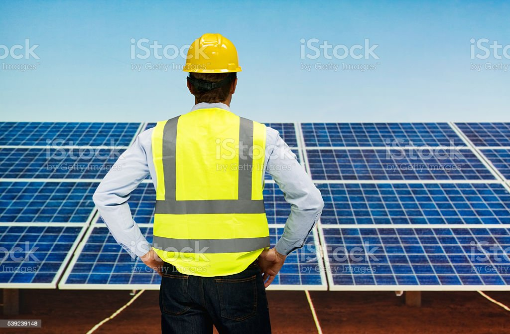 Rear view of solar worker standing outdoors royalty-free stock photo