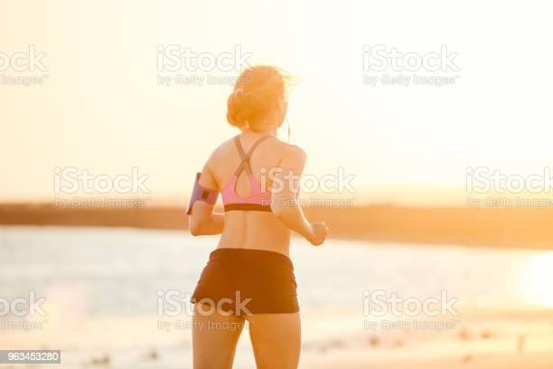 Widok Z Tyłu Sportsmenki W Słuchawkach Ze Smartfonem W Bieganiu Po Obudowie Na Ramię Jogging Na Plaży Przed Światłem Słonecznym - zdjęcia stockowe i więcej obrazów Biegać