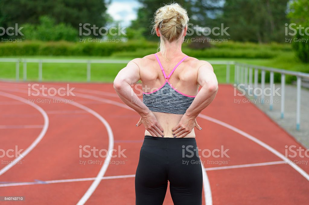 Rear view of sprinter massaging her own back stock photo