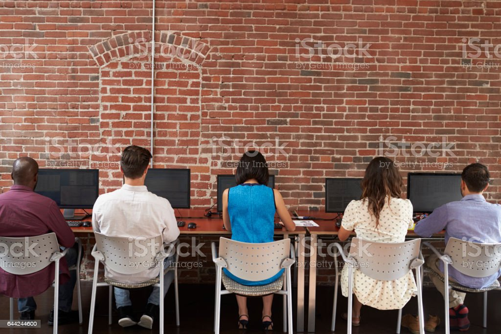 Rear View Of Staff At Desks Using Computers In Busy Office stock photo