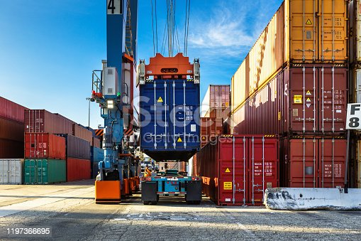 istock Rear View of Straddle Carrier Lifting Container from Truck 1197366695