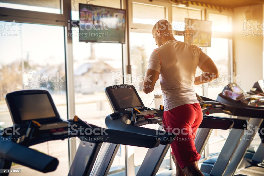 Rear view of strong motivated and focused muscular bald bodybuilder man running on the treadmill with earphones in the modern sunny gym with tv in front. stock photo