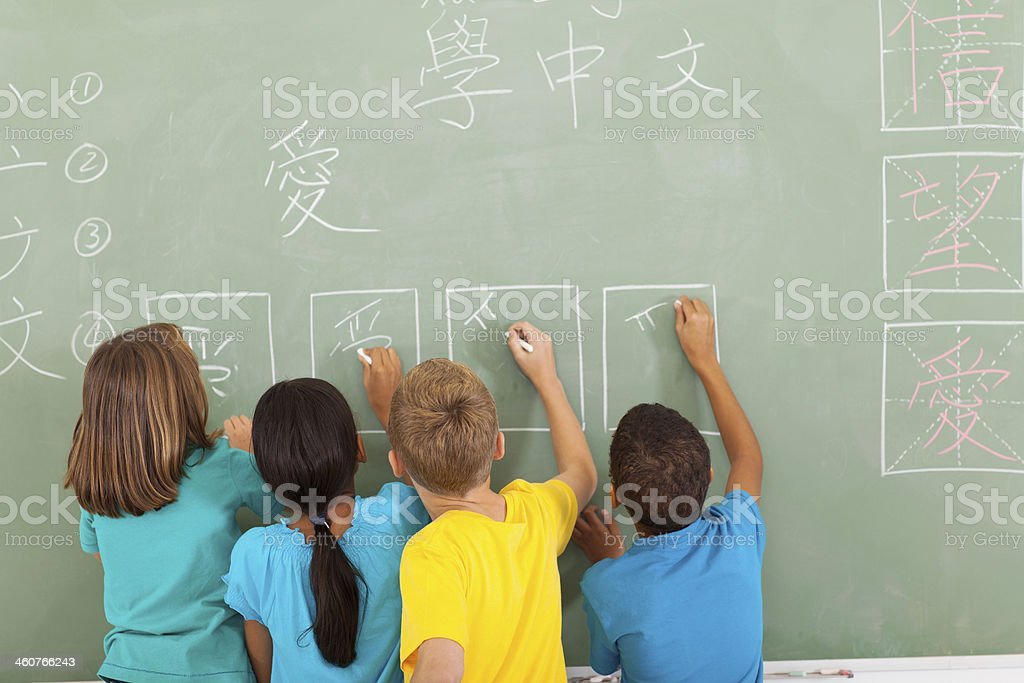 rear view of students learning chinese writing on chalkboard stock photo