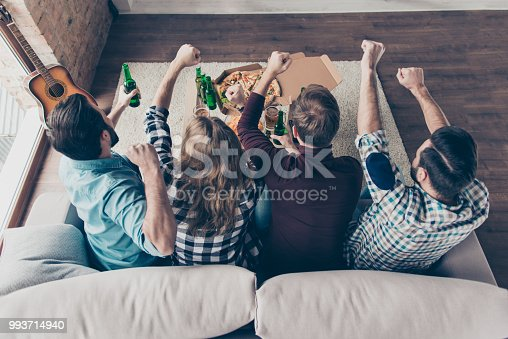 istock Rear view of stylish, successful, attractive four guys with raised arms, cheer for favorite team, watching football, hockey match together, shouting, screaming goal, drinking lager eating snacks 993714940