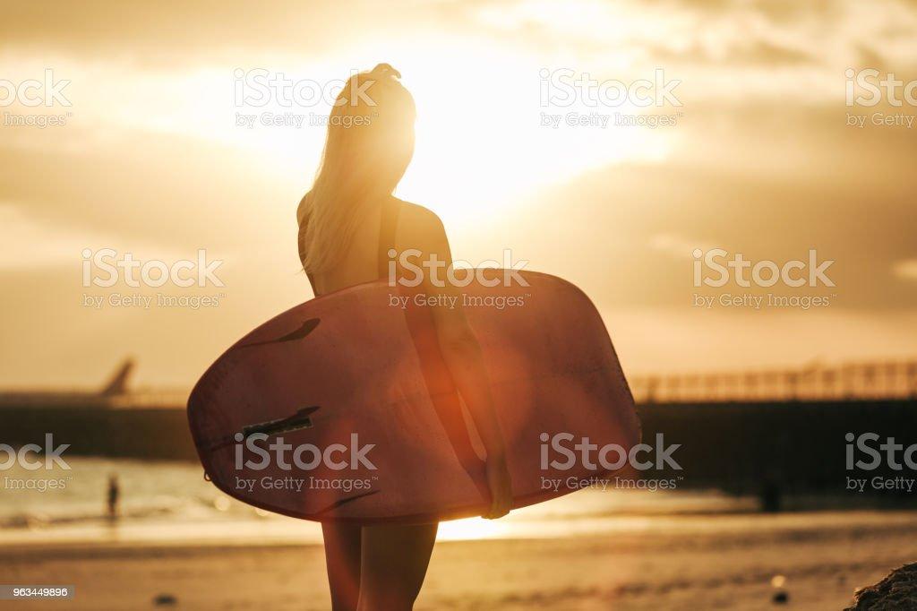 widok z tyłu surfer pozowanie z deski surfingowej na plaży o zachodzie słońca z podświetlenia - Zbiór zdjęć royalty-free (Deska surfingowa)