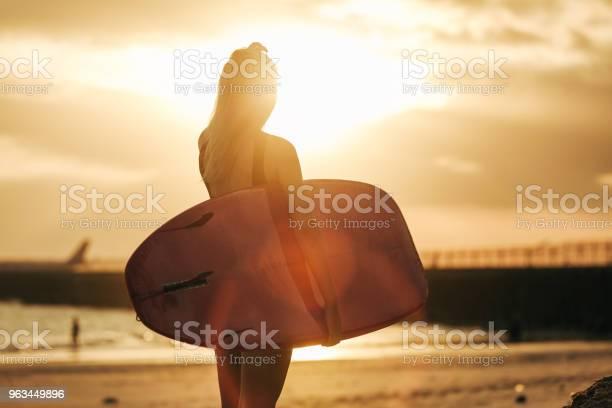 Widok Z Tyłu Surfer Pozowanie Z Deski Surfingowej Na Plaży O Zachodzie Słońca Z Podświetlenia - zdjęcia stockowe i więcej obrazów Deska surfingowa