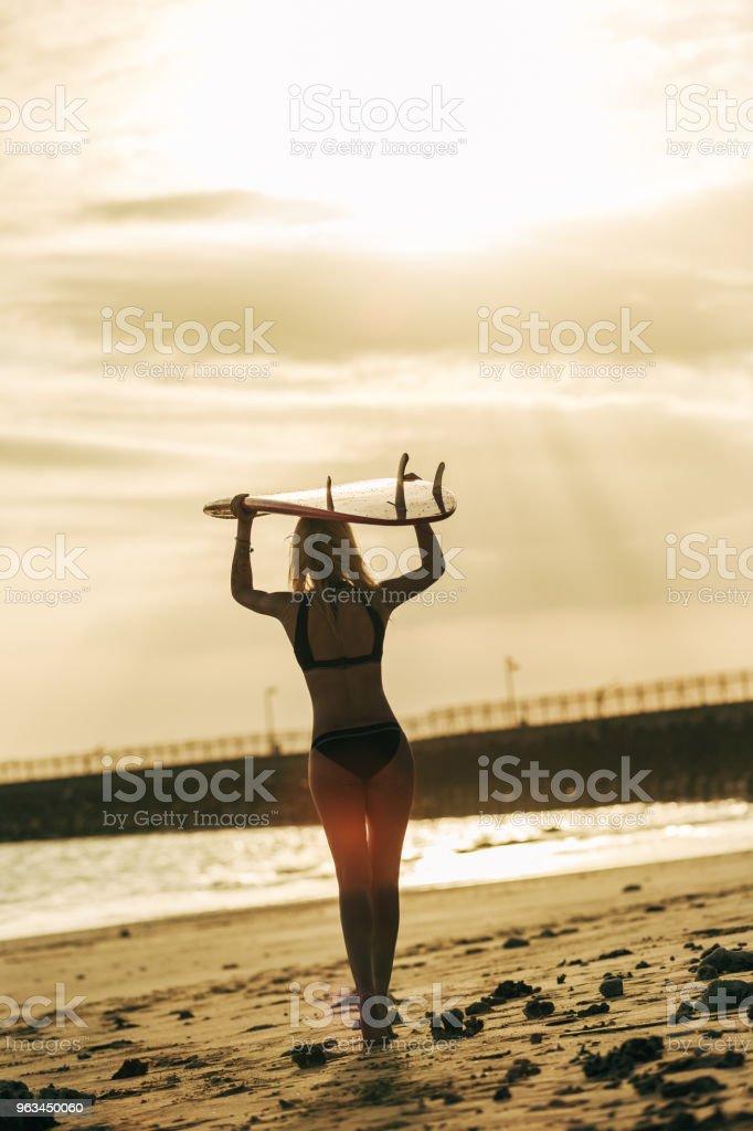 Dikiz Okyanusu yakın gün batımında başına surfboard ile poz sörfçü - Royalty-free Arka Işıklar Stok görsel