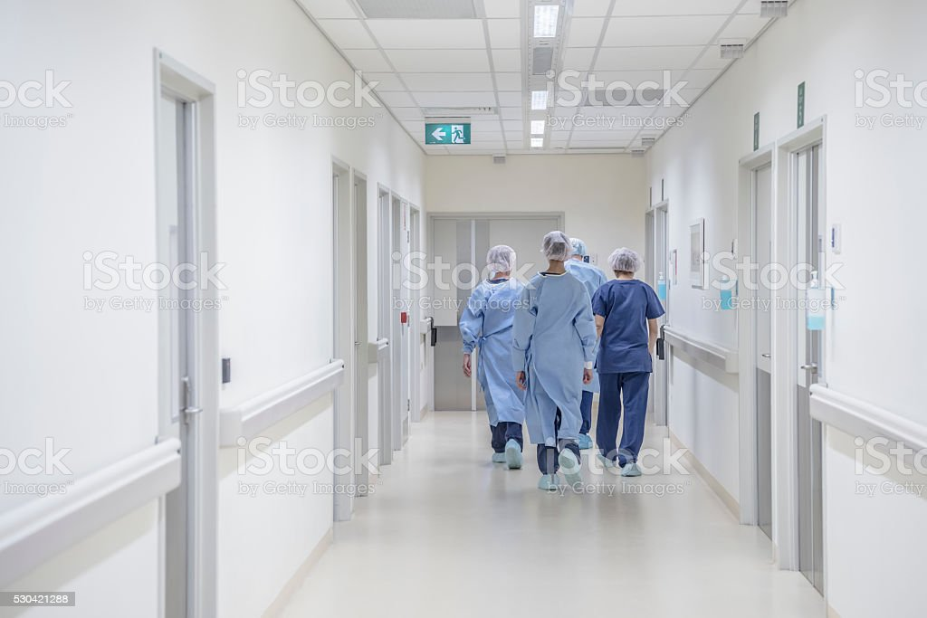 Rear view of surgeons walking down hospital corridor wearing scrubs stock photo