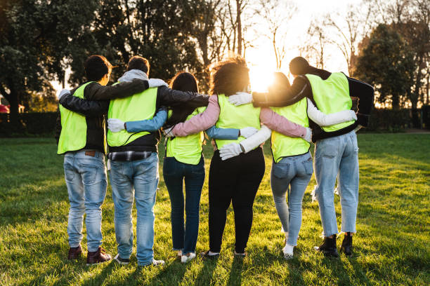 Rear view of teenager volunteers embracing together stock photo