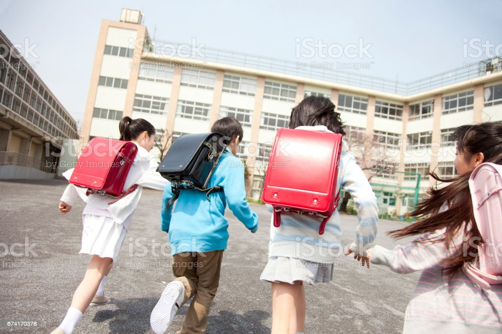 Rear view of the elementary school students go to school four royalty-free stock photo