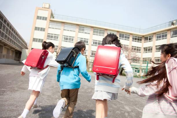 vista posterior de los estudiantes de la escuela primaria van a la escuela cuatro - escuela primaria fotografías e imágenes de stock