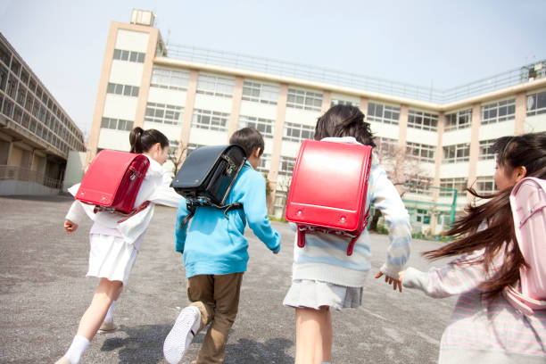 rear view of the elementary school students go to school four - primary school stock pictures, royalty-free photos & images