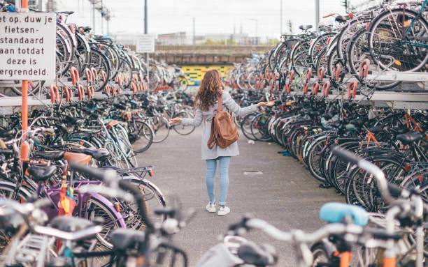 """achteraanzicht van het meisje verloor haar fiets op de fietsparking in eindhoven city (nederland)-bike chaos in holland concept-teken: """"pas op, duw je fiets stand tot het vergrendeld is"""". - eindhoven city stockfoto's en -beelden"""