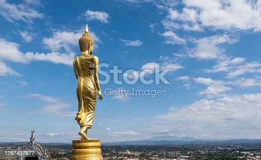 istock Rear view of the golden standing Buddha statue. 1297437677