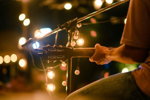 widok z tyłu siedzącego mężczyzny grać na gitarze akustycznej na koncercie na świeżym powietrzu z mikrofonem stanąć z przodu, koncepcji muzycznej. - muzyka zdjęcia i obrazy z banku zdjęć