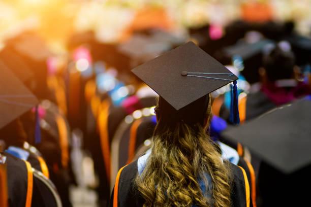 vista trasera de la universidad graduados se alinean para el premio de grado en la ceremonia de graduación de la universidad. - graduación fotografías e imágenes de stock