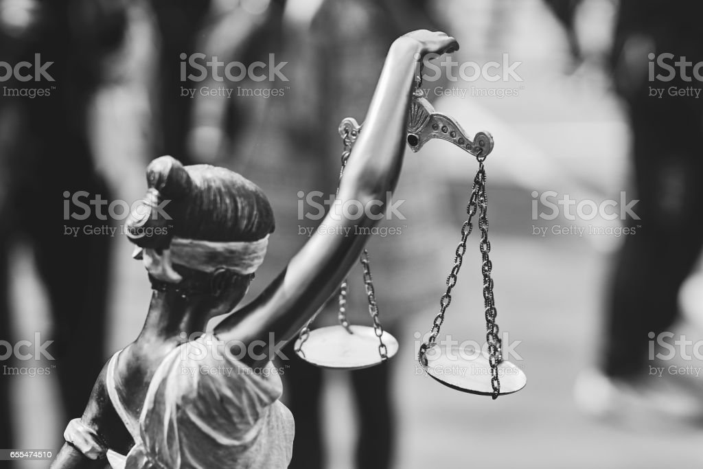 Rear view of themis statue with balance scales in black and white stock photo