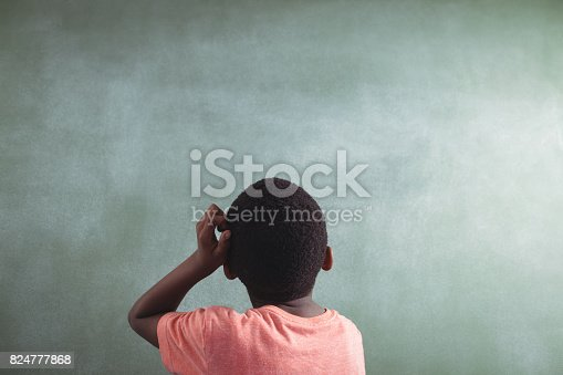 istock Rear view of thoughtful boy against greenboard 824777868