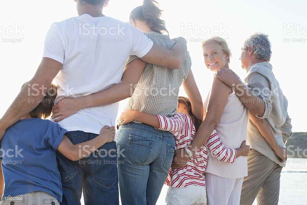 Rear view of three generation family enjoying on beach standing side by side stock photo