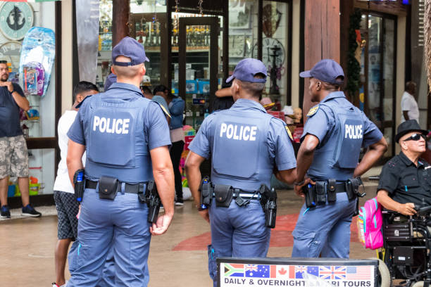 Rear view of three policemen watching over inside the UShaka Marine World in Durban, South Africa. stock photo