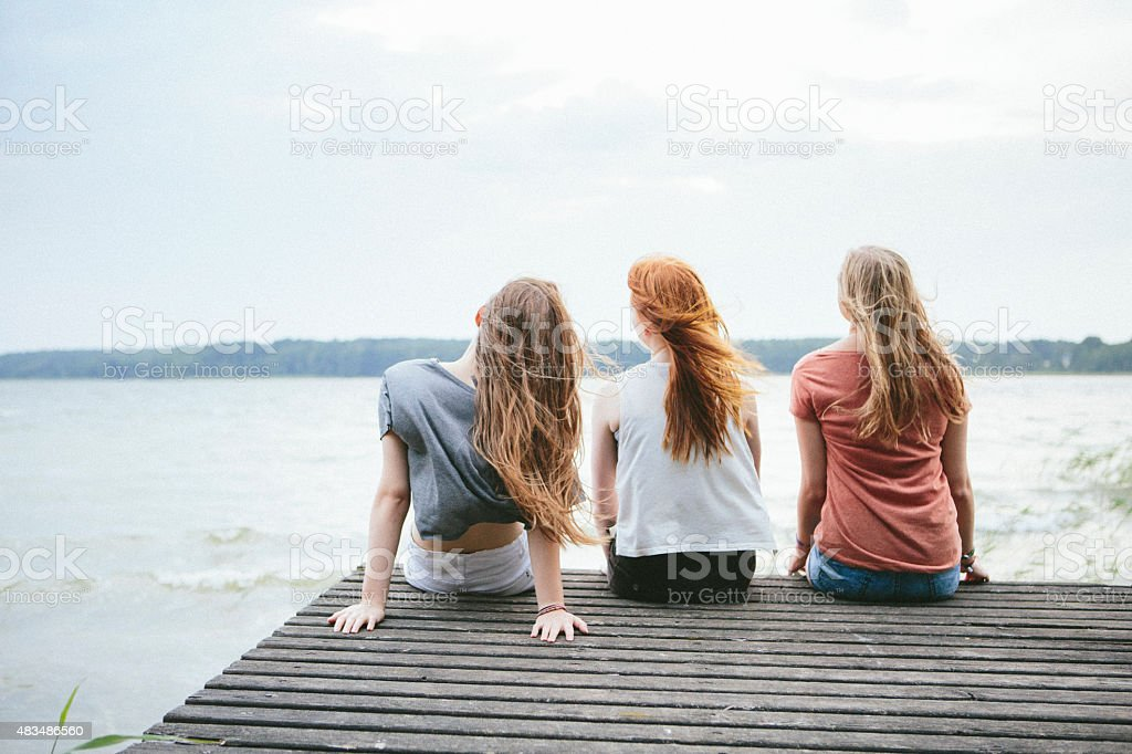 rear view of three teenage girls with blowing long hair stock photo