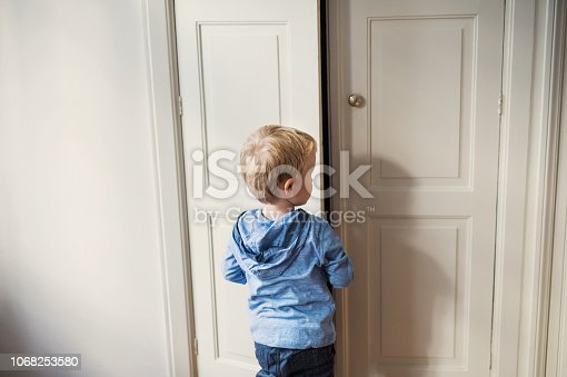 A rear view of toddler boy standing near wardrobe door inside in a bedroom. Copy space.