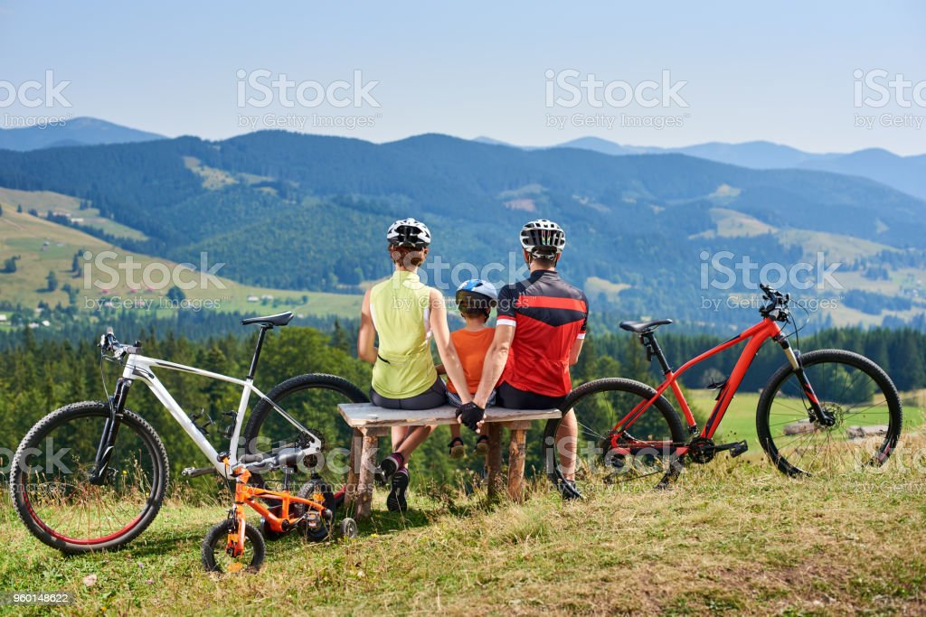 Rear view of tourists, mom, dad and child sitting on wooden bench, resting after cycling bicycles stock photo