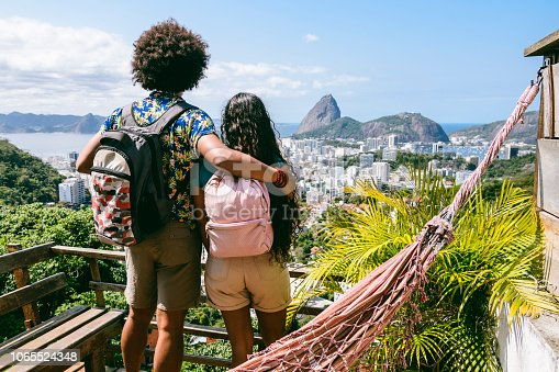 Man and woman wearing backpacks, looking at city scape, elevated view from balcony, on vacation