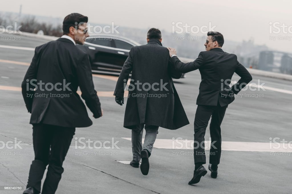 rear view of two bodyguards going with businessman to car stock photo