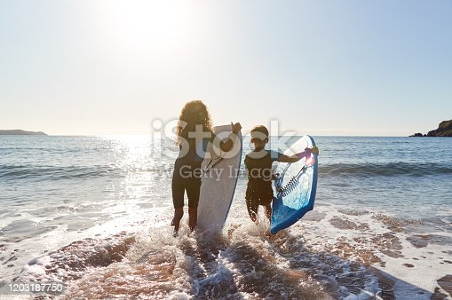 Rear View Of Two Children Wearing Wetsuits Running Into Sea With Bodyboards On Beach Vacation