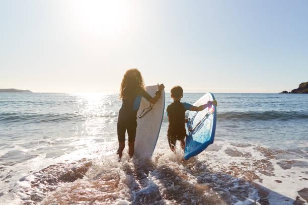 retrovisor de duas crianças usando roupas de mergulho correndo para o mar com bodyboards em férias na praia - esporte aquático - fotografias e filmes do acervo