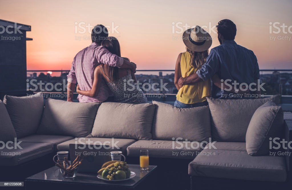 Rear view of two embraced couples looking at sunrise from a penthouse terrace. stock photo