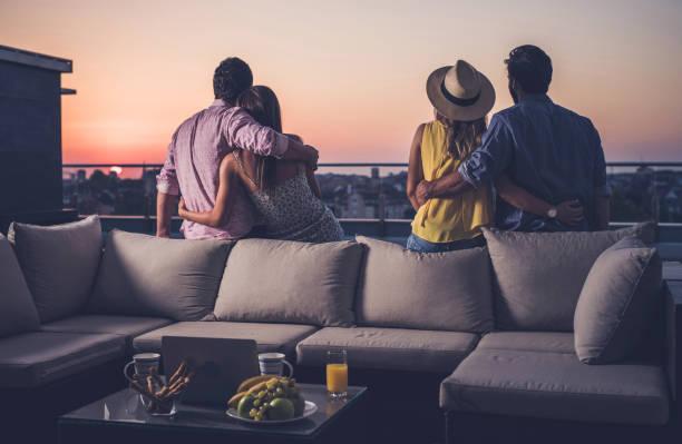 Vista traseira dos dois casais abraçados, olhando para o nascer do sol de um terraço de cobertura. - foto de acervo