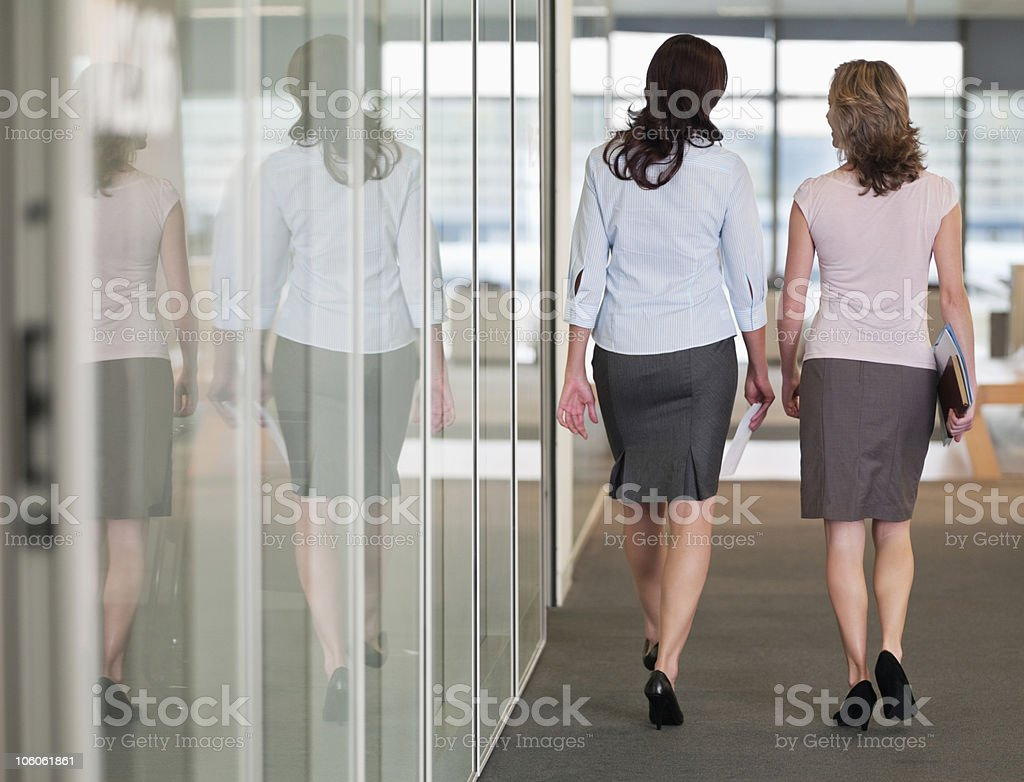 Rear view of two female business colleagues walking in office corridor