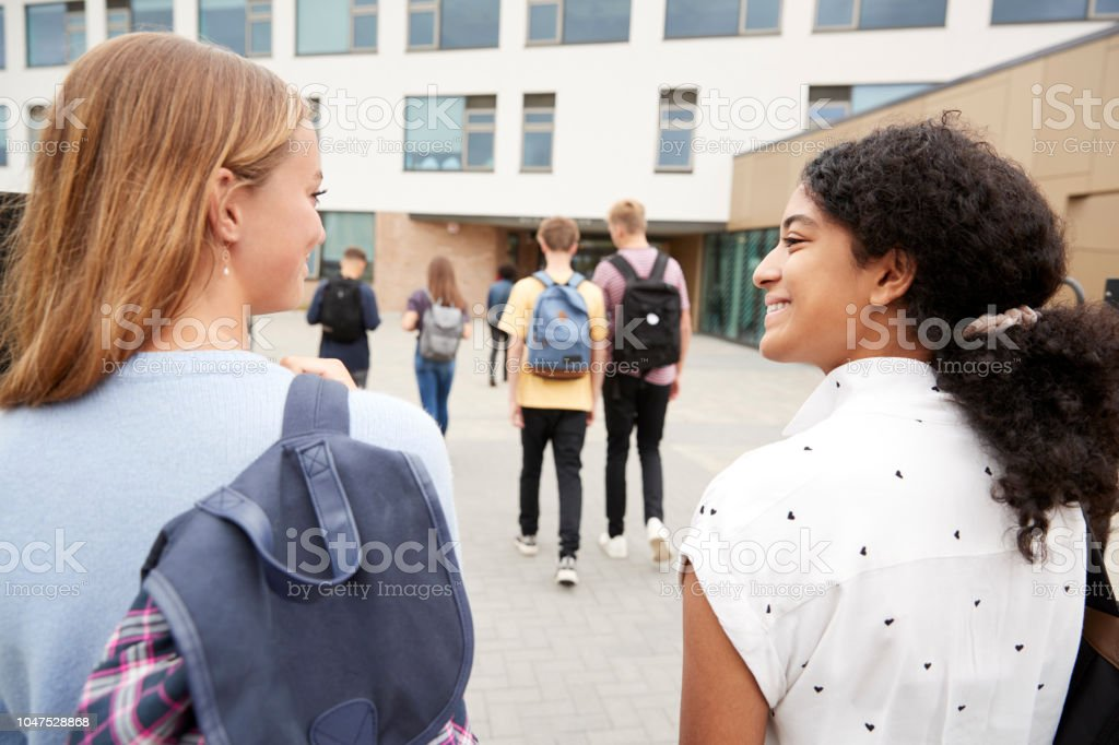 Rear View Of Two Female High School Students Walking Into College Building Together stock photo